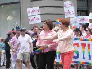 Mayoral candidate Christine Quinn in orange slacks with her spouse Kim Cattullo.