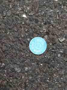 Lucky casino chip in asphalt.