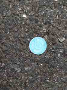 Lucky casino chip in asphalt.