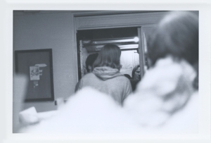 Freight elevator door opened. black speck between hoodie man's shoulder and guy inside is Patti's bowler hat.