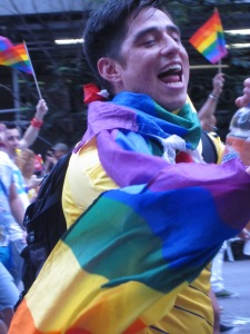 Jubilant marcher all wrapped up in the rainbow flag.